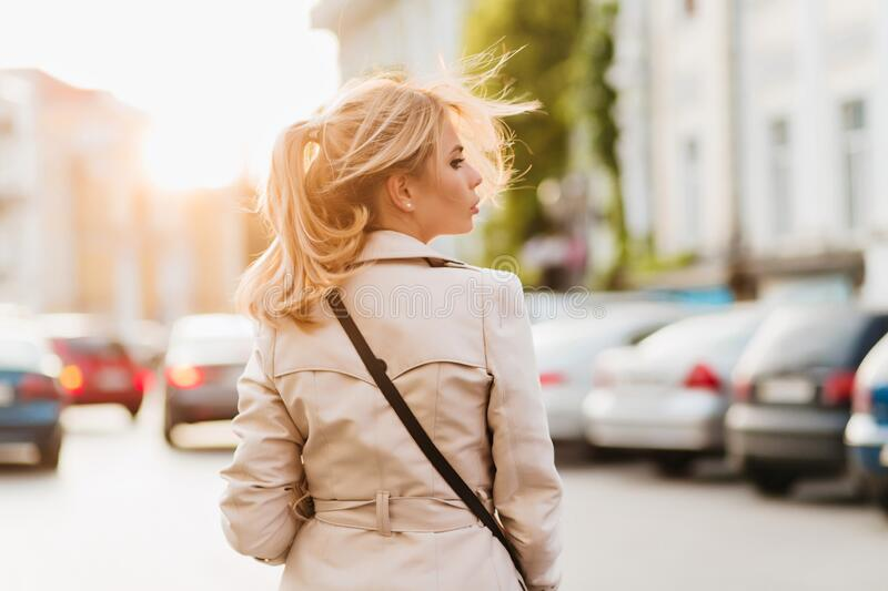 Outdoor portrait from back of serious lady in beige coat looking away standing on the street. Pretty girl with blonde royalty free stock image