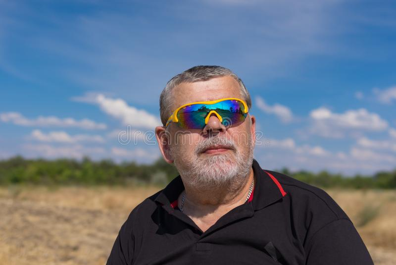 Outdoor portrait of a bearded senior in sunglasses against blue cloudy sky royalty free stock image