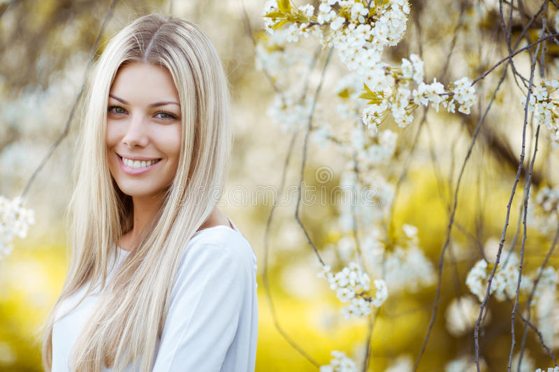 Outdoor portrait of a beautiful blonde woman in blue dress among royalty free stock image