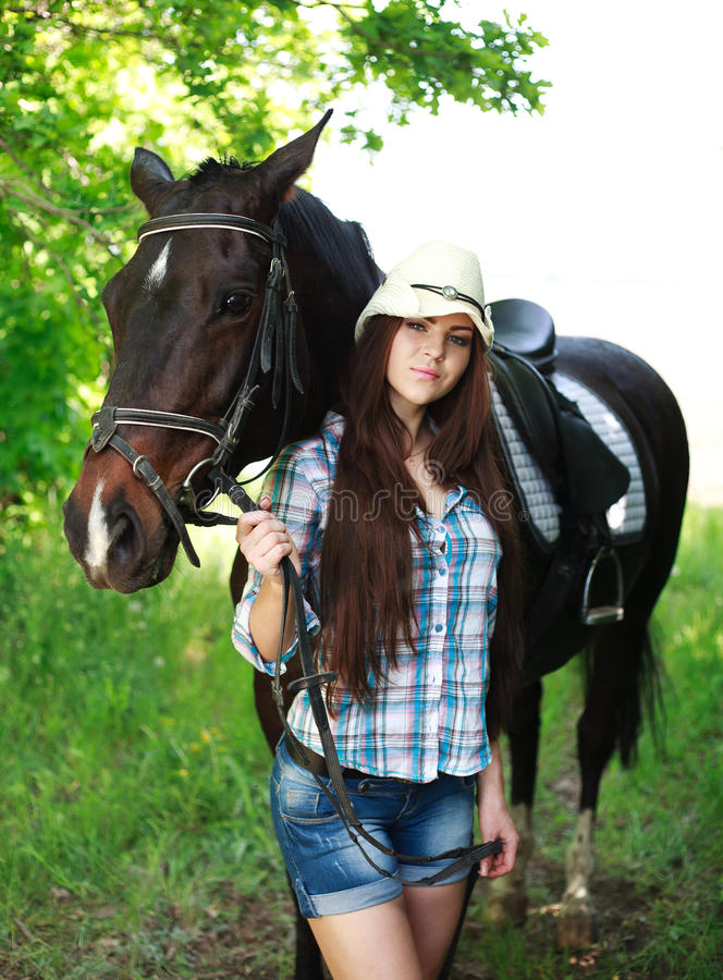 Outdoor portrait of beautiful cowgirl with horse in green. Outdoor portrait of beautiful cowgirl with horse in the green forest royalty free stock photos