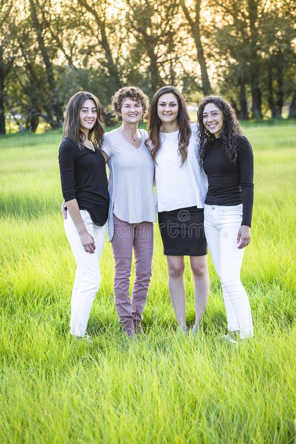 Outdoor Portrait of a beautiful family, a mother and her daughters. Vertical portrait of beautiful hispanic women standing together in a grass field with the royalty free stock photography
