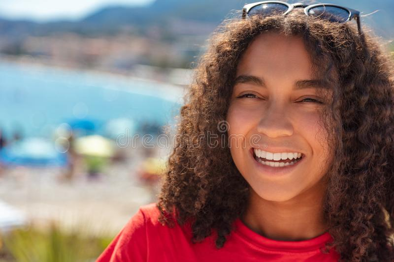 Mixed Race African American Girl Teenager Laughing By Beach. Outdoor portrait of beautiful happy mixed race biracial African American girl teenager female young stock photography