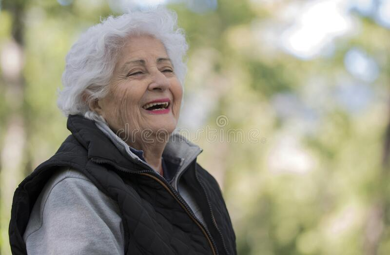 Outdoor portrait of beautiful senior woman with curly white hair. Elderly lady in park royalty free stock photo