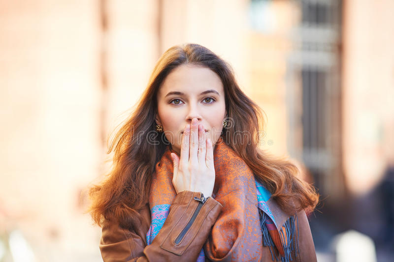 Outdoor portrait of beautiful redhead woman covering her mouth with hand stock image