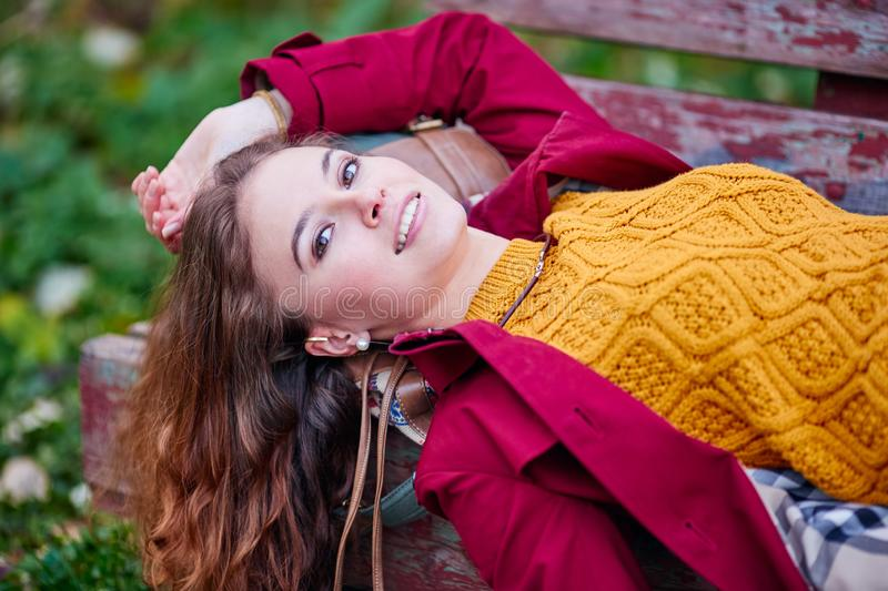 Outdoor portrait of beautiful redhead woman. In red cloak stock photos
