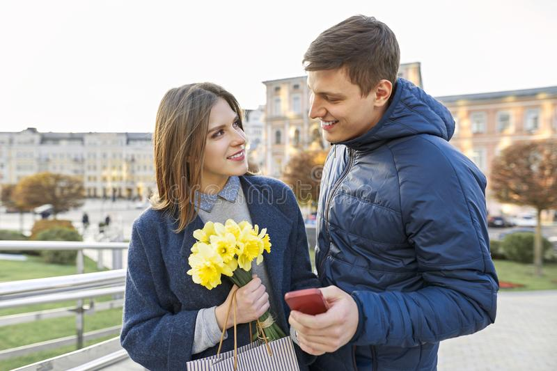 Outdoor portrait of beautiful romantic couple, young man and woman with bouquet of yellow flowers of daffodils and looking in stock photography