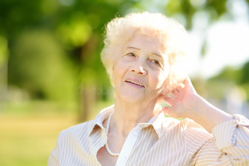 Outdoor portrait of beautiful senior woman with curly white hair royalty free stock images