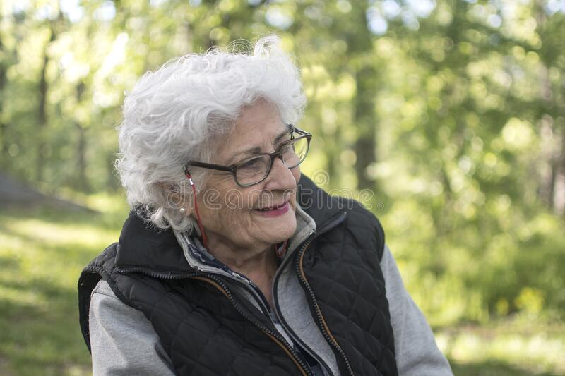 Outdoor portrait of beautiful senior woman with curly white hair. Elderly lady in park royalty free stock images