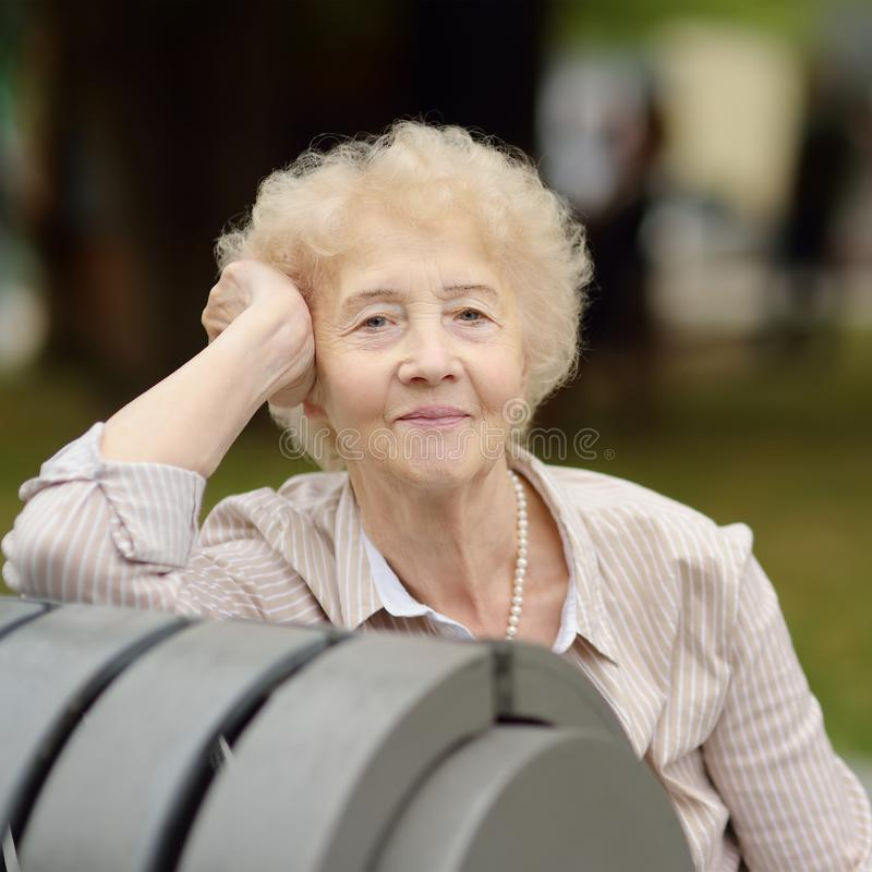 Outdoor portrait of beautiful senior woman with curly white hair stock image