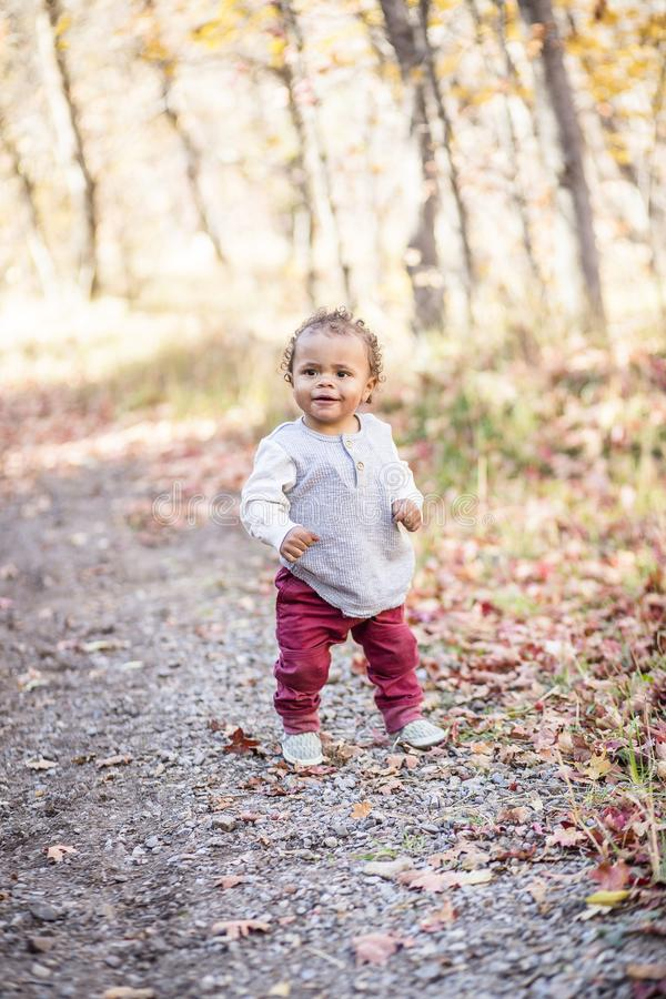 Outdoor Portrait of a beautiful smiling mixed race little boy walking. On a trail. Perfectly adorable child with a very cute expression on his face as he learns royalty free stock image