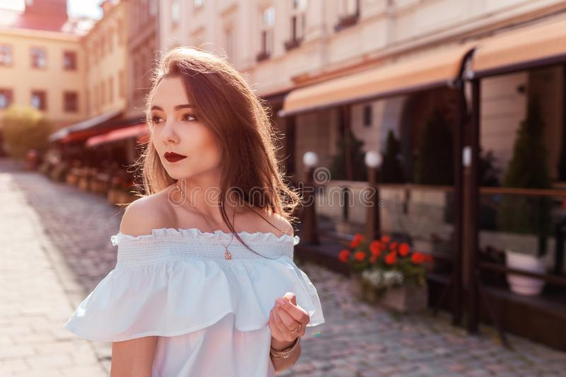 Outdoor portrait of beautiful stylish woman walking on street. Fashion model wearing summer clothing and accessories stock photography