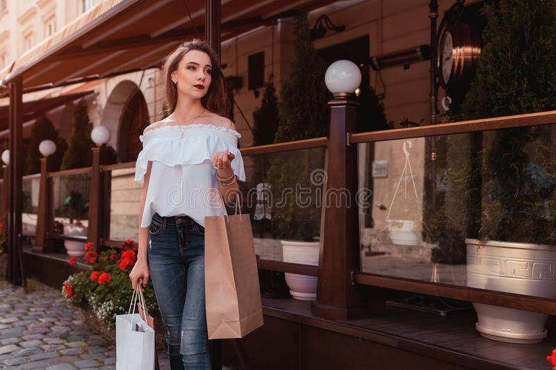 Outdoor portrait of beautiful stylish woman walking on street. Fashion model waiting for friends by cafe stock photo