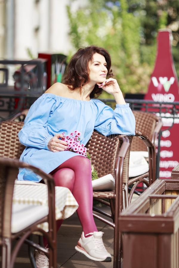 Outdoor portrait of beautiful woman at the table in a street city cafe. Urban romantic portrait of beautiful girl wearing light. Blue dress and burgundy tights stock photos