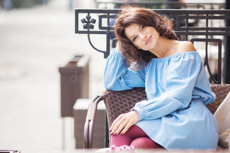 Outdoor portrait of beautiful woman at the table in a street city cafe. Urban romantic portrait of beautiful girl wearing light. Blue dress and burgundy tights royalty free stock photos
