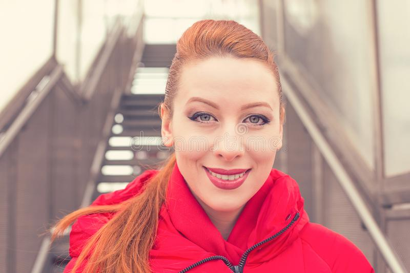 Outdoor portrait of a beautiful woman wearing red coat royalty free stock photos