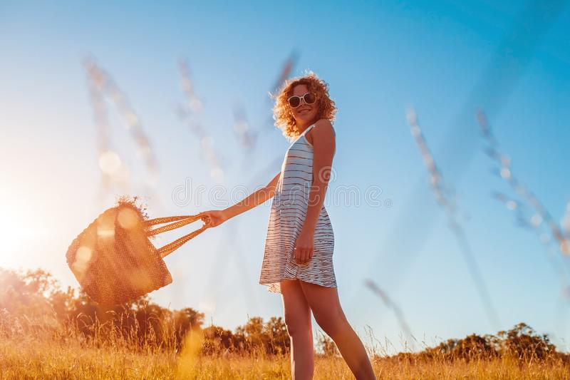 Outdoor portrait of beautiful young woman with red curly hair holding bag with flowers. Summer modern look. Outdoor portrait of beautiful young woman with red stock photography