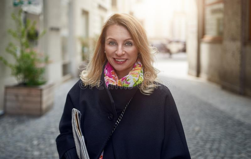 Outdoor portrait of blonde mature smiling woman royalty free stock photography