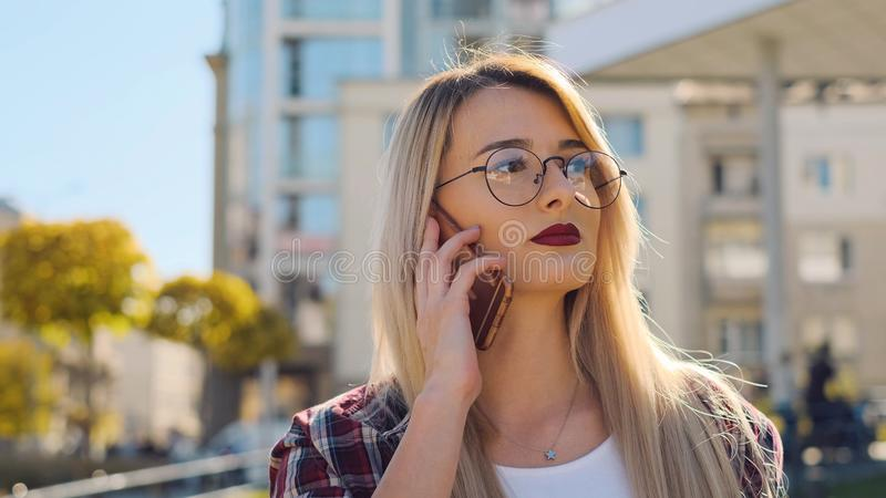 Outdoor portrait a blonde young woman talking by her smartphone stock photography