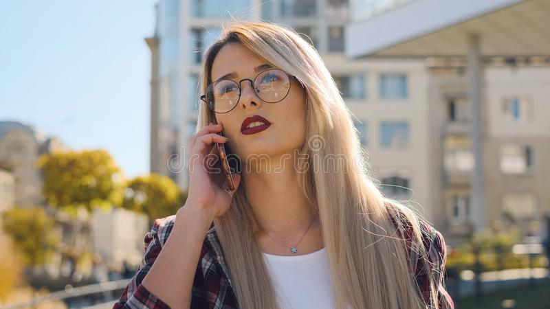 Outdoor portrait a blonde young woman talking by her smartphone royalty free stock images