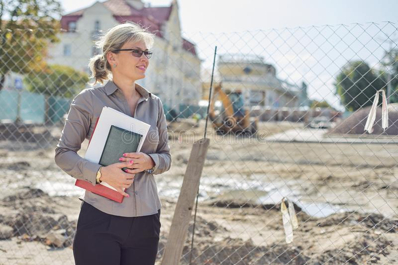 Outdoor portrait of business mature woman, paving stone laying stock images
