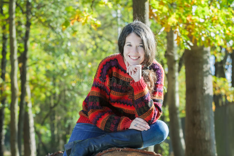 Outdoor portrait of cheerful young woman sitting on sawn tree trunk royalty free stock image
