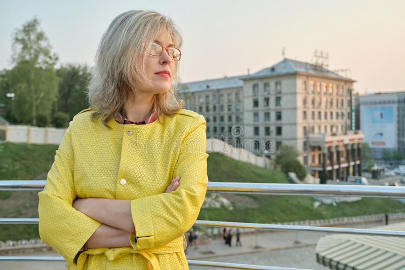 Outdoor portrait of confident mature woman with folded hands. Beautiful smiling age woman with glasses, arms crossed, background. City panorama, copy space stock image