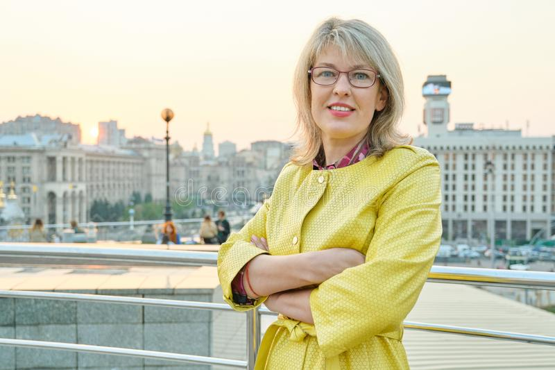 Outdoor portrait of confident mature woman with folded hands. Beautiful smiling age woman with glasses, arms crossed, background. City panorama, copy space stock photography