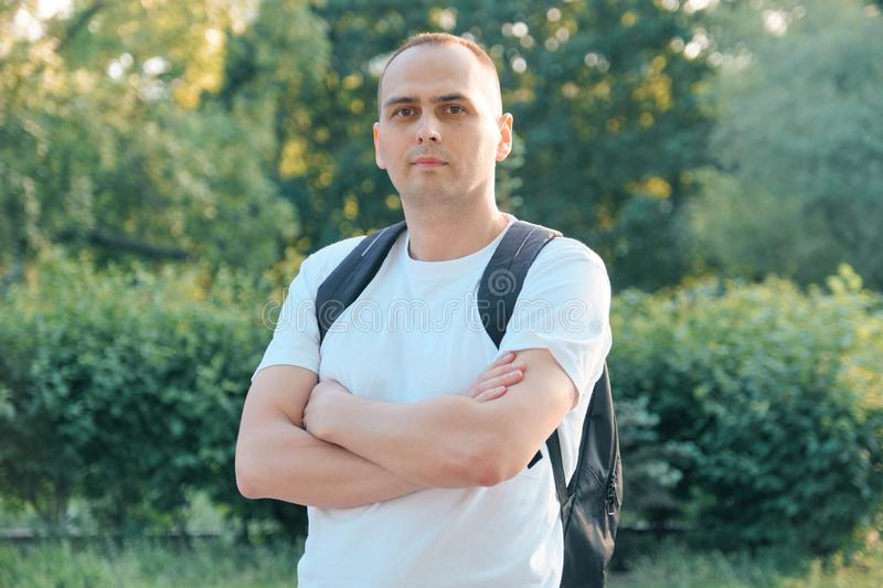 Outdoor portrait of confident middle-aged sports man. Handsome male with arms crossed in white t-shirt looking at the royalty free stock photos