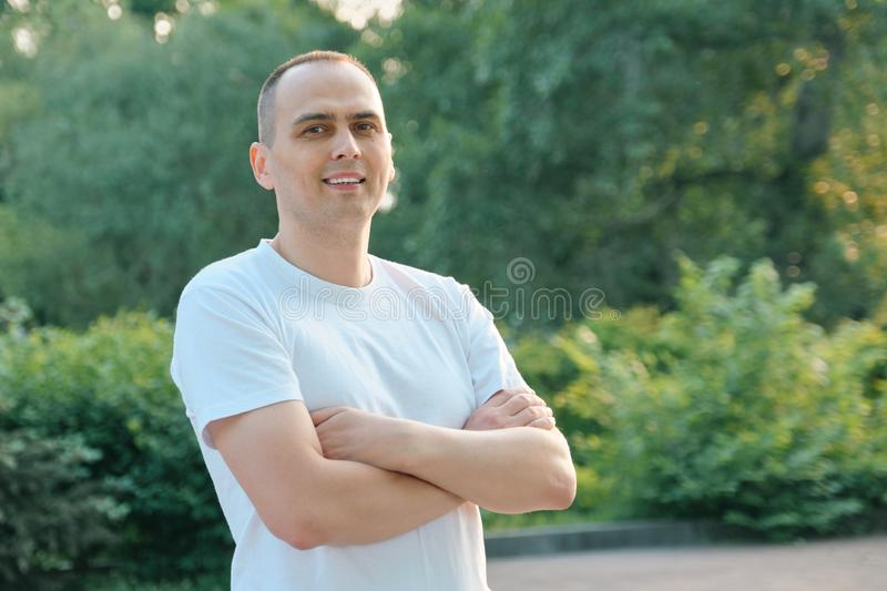 Outdoor portrait of confident smiling middle-aged sports man. Positive handsome male with arms crossed in white t-shirt looking at royalty free stock images