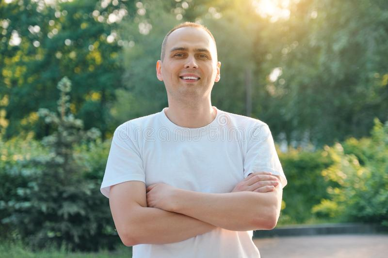 Outdoor portrait of confident smiling middle-aged sports man. Positive handsome male with arms crossed in white t-shirt looking at royalty free stock photos
