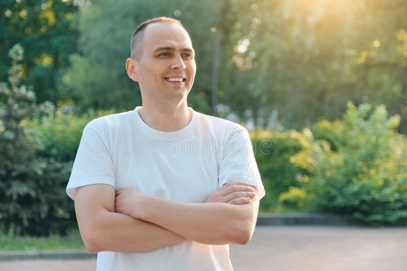 Outdoor portrait of confident smiling sporty man of 40 years. Positive handsome male with arms crossed in white t-shirt royalty free stock images