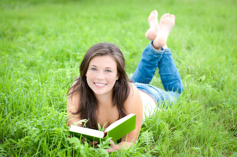 Outdoor portrait of a cute reading teen royalty free stock photo