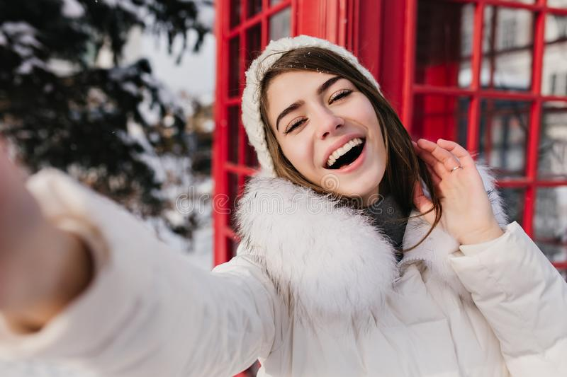 Outdoor portrait of cute woman with happy smile making selfie in London during winter vacation. Adorable girl in white royalty free stock photography