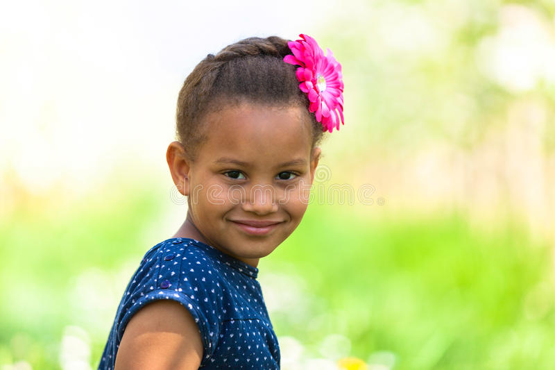 Outdoor portrait of a cute young black girl smiling - African pe stock photo