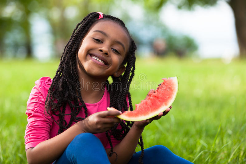 Outdoor portrait of a cute young black little girl eating watermelon - African people royalty free stock photo