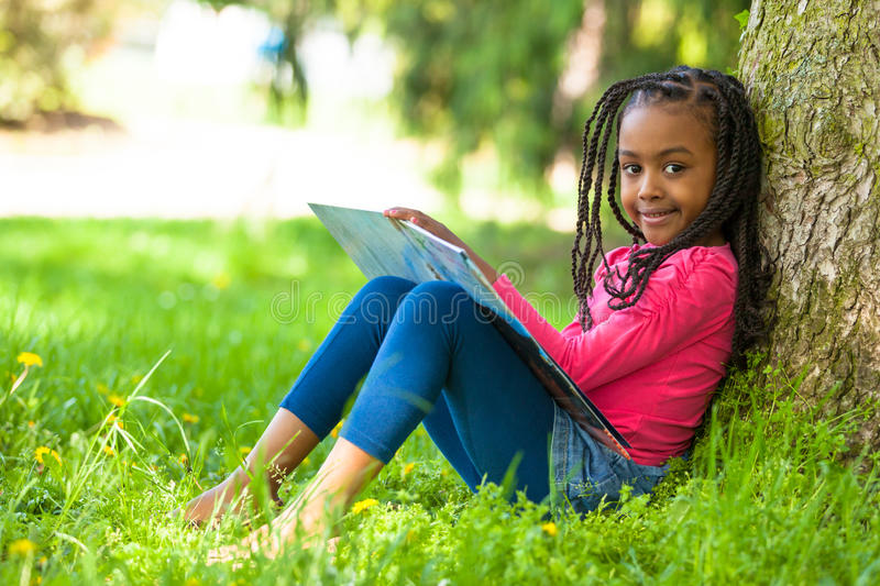 Outdoor portrait of a cute young black little girl reading a boo. K - African people royalty free stock photography
