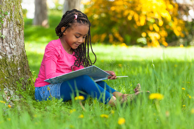 Outdoor portrait of a cute young black little girl reading a boo royalty free stock photos