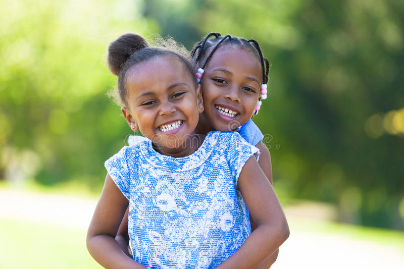 Outdoor portrait of a cute young black sisters - African people stock images