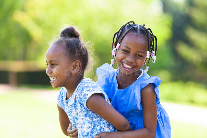 Outdoor portrait of a cute young black sisters - African people royalty free stock photos