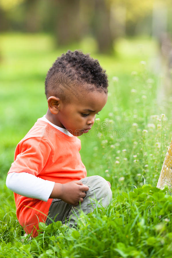 Outdoor portrait of a cute young little black boy playing outsi royalty free stock photo