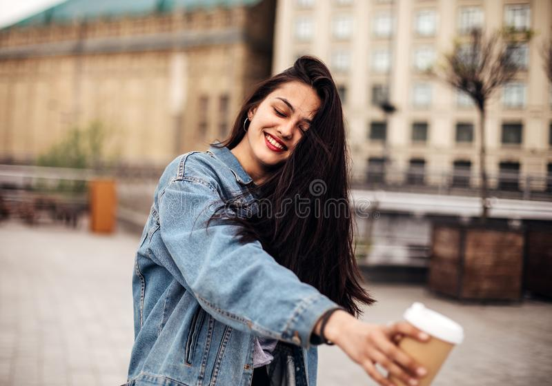 Outdoor portrait of a dark-haired young woman in a denim jacket holds coffee to go. Emotional woman posing with happy smile on the royalty free stock photography