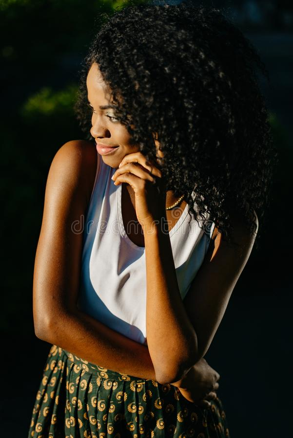 Outdoor portrait of the dreamy charming afro-american girl with green eye shadows and long dark curly hair looking aside royalty free stock image