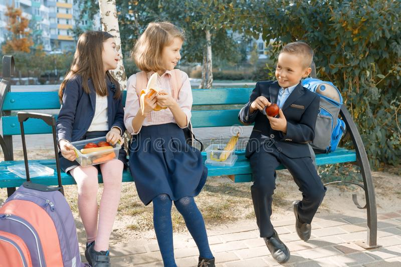 Outdoor portrait of elementary school students with lunch boxes, healthy school breakfast. Children eat, talk, laugh stock image