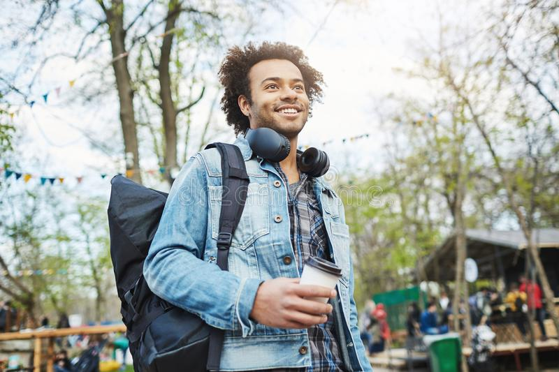 Outdoor portrait of fashionable african-american man with afro haircut, wearing denim coat and backpack while holding. Coffee and looking aside, walking in park stock images