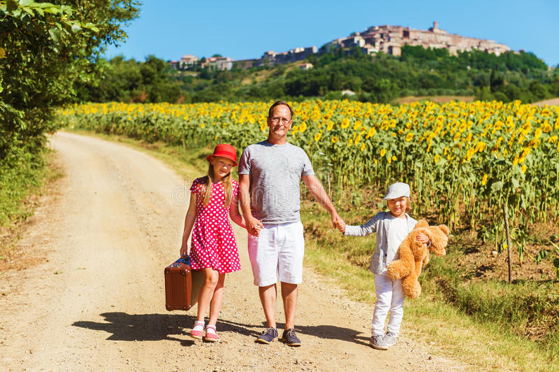Outdoor portrait of a funny little kids and the father walking down the road stock photo