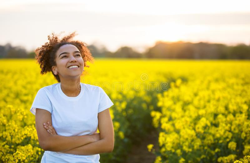 Mixed Race African American Girl Teenager Smiling Happy In Yellow Flowers stock image