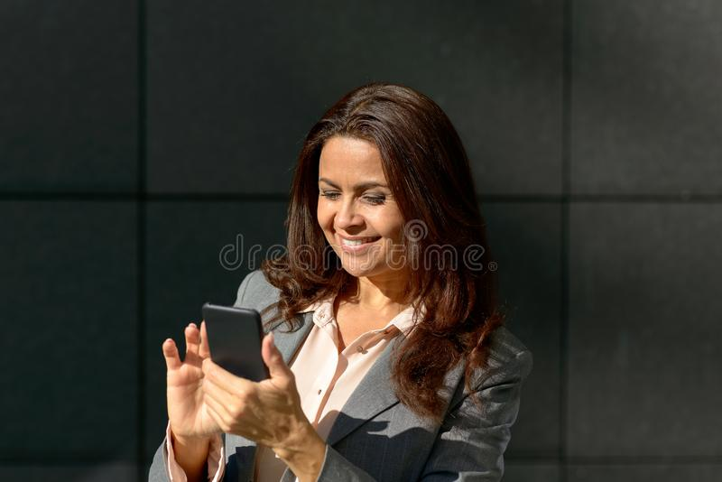 Happy adult woman using smartphone. Outdoor portrait of a happy adult woman using smartphone stock photos