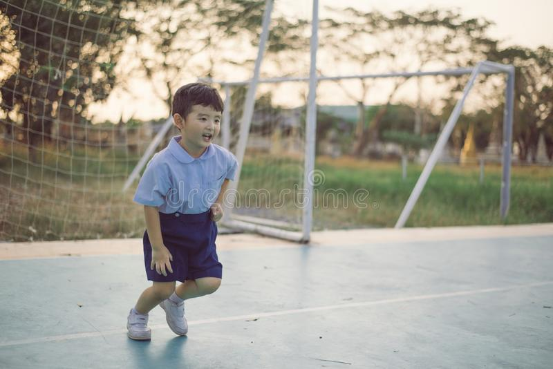 Outdoor portrait of a happy Asian student kid in school uniform smiling stock image