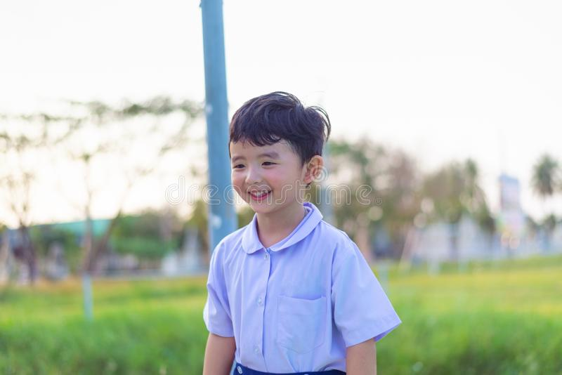 Outdoor portrait of a happy Asian student kid in school uniform smiling stock photography