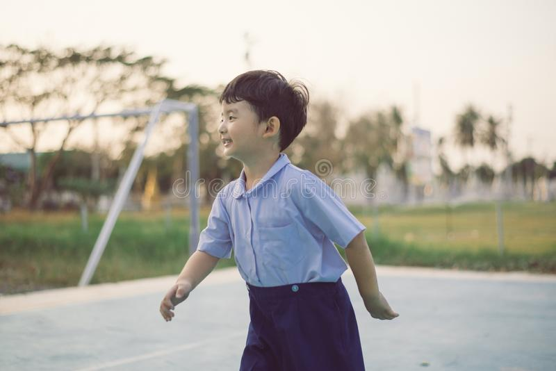 Outdoor portrait of a happy Asian student kid in school uniform smiling royalty free stock photos